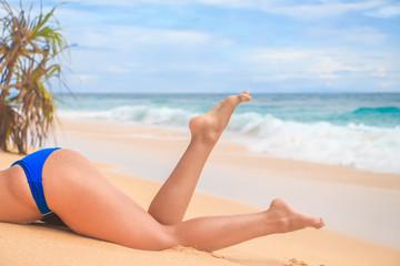 Woman legs on sand ocean beach. Close up. Travel concept.