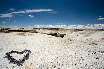 heart made of pebbles in a rock desert in the USA with a blue sky behind