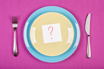 colorful stock image of sticky note with question mark lying on a plate. diet concept