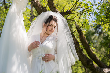 A fantastic bride in the park sits on the swing and looks at the wedding dress
