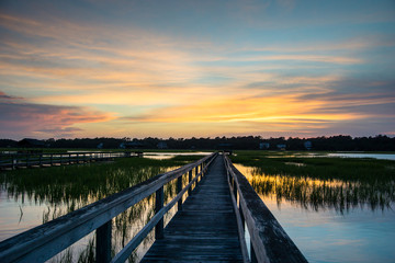 boardwalk leading into tidal basin of a barrier island filled with marsh grass under a beautiful sky at sunset in South Carolina