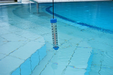A thermometer immersed in water in the pool