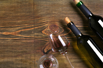 Bottles and two glasses of wine on wooden background from top view