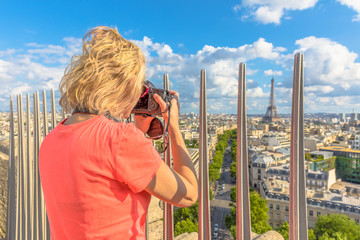 Travel woman professional photographer takes photos from top of Arc de Triomphe. Female photographer with camera in French capital, Europe. Popular travel destination. Paris skyline aerial view.