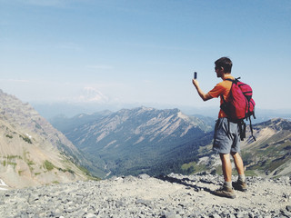 Male hiker standing on mountain summit, taking photographs with smart phone