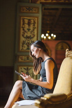 Young businesswoman working with digital tablet at beautiful baroque room.