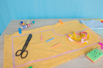 Tools for sewing for hobby set on wooden table background top view. Sewing kit. Thread, needles and cloth