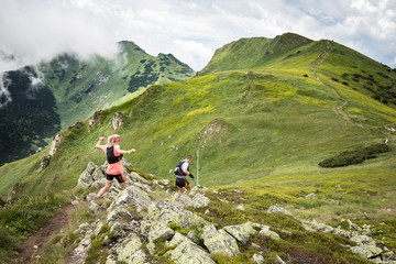 man and woman running together on beautiful high mountain trail with clouds after summer storm