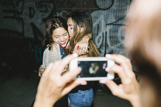 Playful female friends using a phone as camera on Saturday night