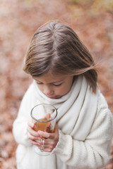 Girl holding mug of hot apple cider