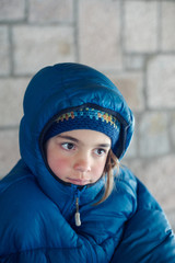 Portrait of a young girl with hood and down jacket on a cold day