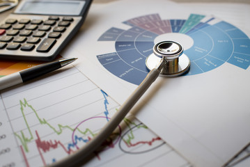 Medical practice financial analysis charts with stethoscope and calculator
