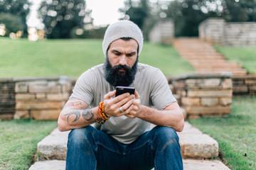 Tattooed man in a hat using a smartphone
