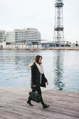 Young woman with winter clothes walking on the dock.