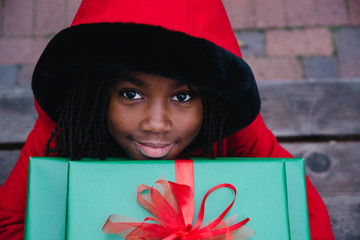 African American in red coat girl holding Christmas gifts
