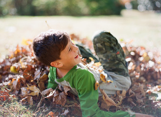 Young boy laughing as he jumps into a pile of leaves