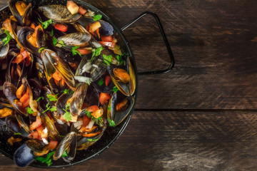 Skillet of marinara mussels on rustic background with copyspace