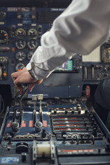 Airplane pilot's hand pushing thrust during take off