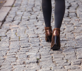 Closeup of legs of a young woman walking away on the street