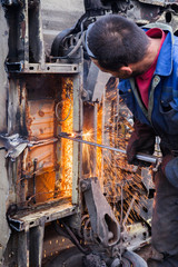 A worker uses a cutting torch to get through a metal construction
