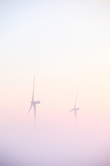 Two windmills at sunrise in cold winter fog
