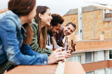 Group of friends having fun drinking beer on a rooftop.