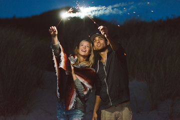 Young couple on beach with sparklers in the summer