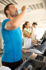 woman and man biking in the gym, exercising legs doing cardio workout