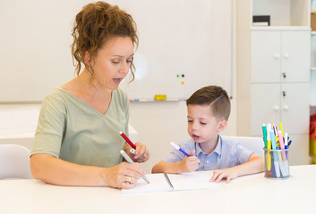 teacher woman drawing with child boy in a classroom