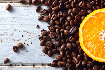 Roasted coffee beans with half orange over a white wood table