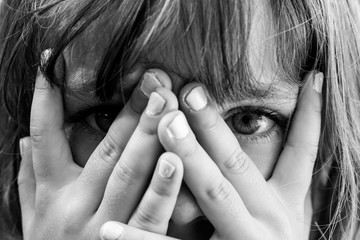 Conceal and reveal: Black and white close up portrait of a young girl hiding behind her hands