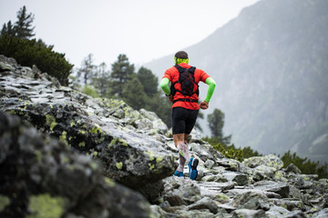 man running on high mountains  outdoor track in bad weather with fog and rain
