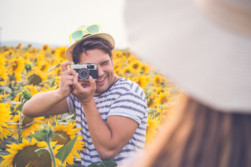Man taking photo of his girlfriend in sunflower field