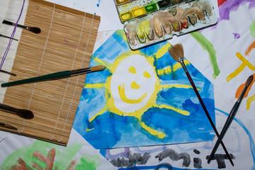 Kinderbild von Sonne auf dem Pinsel und Aquarellfarbe liegen