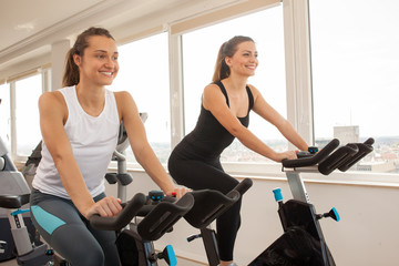 Young  woman biking in the gym, exercising legs doing cardio workout