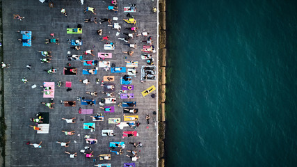 top view of large group of people practice yoga on sea coast