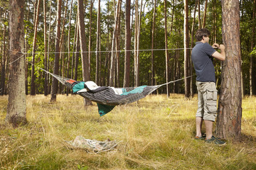 Man in wild forest going to make roof above hammock bed hanged on trees