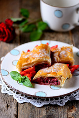 Puff pastry pie with strawberries, nuts and powdered sugar.