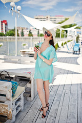 Portrait of an attractive woman in transparent turquoise dress posing with a cocktail in her hand by the lake.