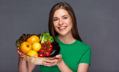 Young woman holding basket with vegetables.