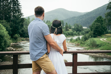 man with woman stands on the bridge across the river