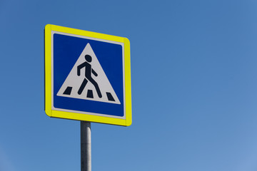 pedestrian crossing sign on a clear day against the sky