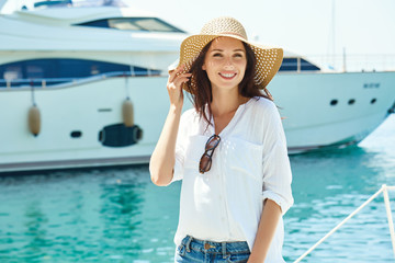 Smiling young woman on the background of a large cruise ship. Boat trip during the summer.
