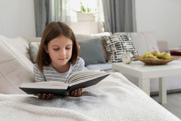 Cute young girl reading book at home