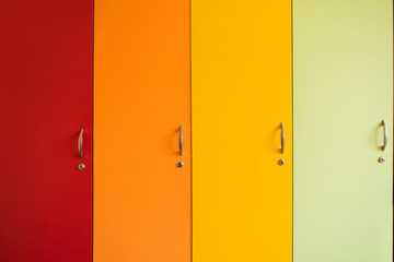 Colorful bright doors of cabinets with handles. Rainbow furniture in kindergarten or school. Bright background of yellow orange, red and green