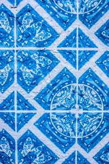 Tiles with typical geometric blue and white shapes of the houses in Portugal