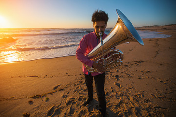 Musician instrumentalist playing the Tuba on the sea coast.