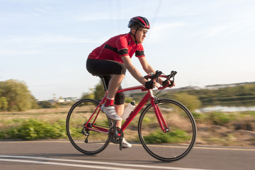 Cycling Concepts. Professional Male Cyclist in Racing Outfit During a Ride on Bike Outdoors. Panning Technique Used.