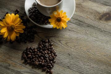 Filiżanka kawy z żółtymi kwiatami w tle.