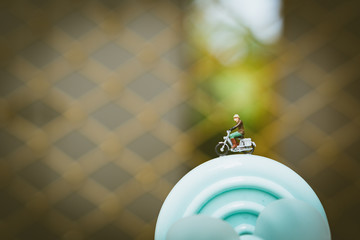 Miniature people, man riding on turbine using for tourism concept - Vintage filter